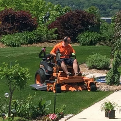 Jeremy Bruce, the owner of Midwest Lawn Pro riding a commercial mower on a customer lawn.
